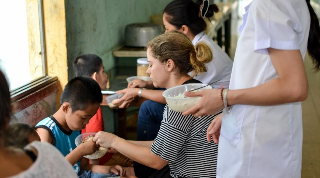 Pictured here is a Projects Abroad intern helping a young boy learn how to eat with limited arm movement whilst she undertakes her occupational therapy internship in Vietnam.